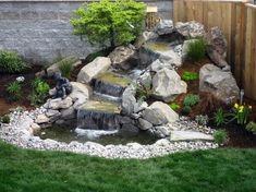 petite cascade de jardin en pierre naturelle décorée de cailloux et végétaux