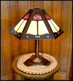 "This 20"" high, two socket table lamp has a six-sided hammered and riveted shade with a long stem rose motif. The art glass used in this example is one of many possibilities, including single color glass or amber mica panels. With two 60 watt bulbs, this lamp provides plenty of light to read by or turn the dimmer down for a more ambient look. This lamp is priced at $2390. (Gorgeous, but too spendy for my budget.)"