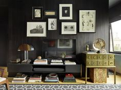 Designer Jay Jeffers stored books under a floating cabinet to make room above for a striking lamp with an oversize shade in his San Francisco home.