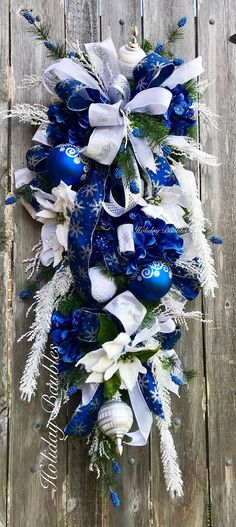 "❄️Gorgeous Royal Blue Frost Swag❄️ 42"" Length Designed on a evergreen teardrop Swag Accented with snow drift poinsettias, blue glitter hydrangeas, blue berries evergreen sprays and snow drift branches through out swag. Embellished with royal blue with silver scroll, snowball and"