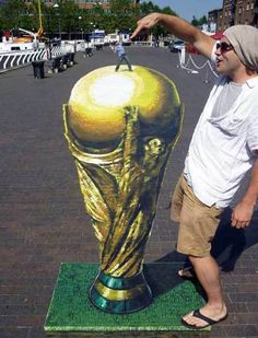 This anamorphic piece shows somewhat of both anamorphic perspectives, and forced perspective because a human looks so small, and the trophy or ball in the hand looks very real. This drawing was done with a lot of effort, and hard work!