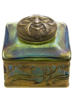 An Austrian Glass and Gilt Metal Inkwell, Attributed to Loetz, having a circular lid decorated with a satyr mask over the square body with repeating stylized lotus decoration. Width 3 1/4 inches.