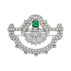 "Art Deco Emerald Diamond Panel Brooch. Deco-style open fan-shaped emerald and diamond panel brooch, centering an emerald-cut emerald weighing approximately 0.59 carats, with circular-cut, half moon-shaped, baguette-cut and marquise-shaped diamonds weighing approximately 6.44 total carats, mounted in platinum. 1.75"" length and 1.35"" width at widest point."