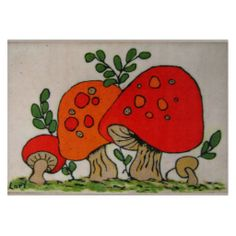 A glass cutting board featuring a Folk Art depiction of orange and red toad stools in ceramic on copper. Sprigs of green leaves accompany the spotted caps and wrinkled stems by artist Lori Parish.