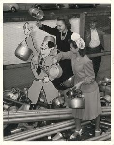 1944- Women aim their pots at an effigy of Hitler during an aluminum drive in San Francisco.