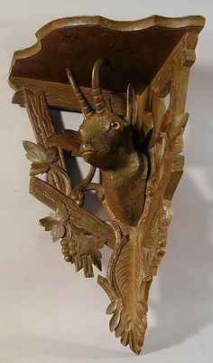 an antique black forest carved wood corner shelf with chamois head