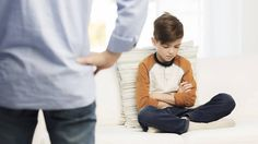 A frustrated boy sits angrily at home in front of his dad.