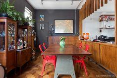 Sala de jantar integrada tem paredes pretas e móveis vintage.