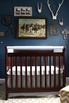 Totally in love with the color on the walls in this nursery (Benjamin Moore's Van Deusen Blue mixed in aura flat), and the general vibe. Not exactly my style, per se, but I love that it's so family-focused.