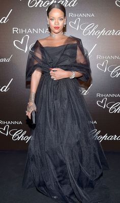 RIHANNA : They say you're never fully dressed without a smile, but when you're Rihanna, you're never fully dressed without millions of dollars of Chopard diamonds, which the superstar wears with a voluminous black tulle gown at the Rihanna x Chopard Collection party.