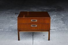 <p>This charming 1950's teak side table has just been refinished and is in excellent condition. It features two dovetailed drawers and bronze banding.</p>
