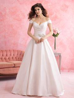 This satin ballgown achieves a deeply romantic effect with its off-the-shoulder sleeves and ruched bodice.