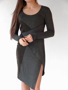 Rayon jersey and silk charcoal gray knee length dress. Super soft materials for movement and comfort. Flattering diagonal lines with side slit. Belt can be tied in front or back. Can be dressed up or worn casually. By Erin Draper.
