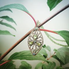 """Cathy Waterman's """"Scattedred Petals"""" pendant with peridots. diamonds, opal and 22-kt gold"""