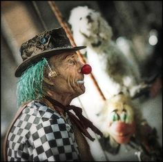 Old Time Clown    The checkerboard costume and touches of clown makeup give a look of faraway times to the face of this sad old clown.