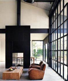 contemporary modern loft interior with open fire place and vintage leather club chairs.