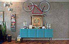 Acima do bufê azul, uma bicicleta rouba a cena desta sala. Dois ganchos foram instalados no teto para sustentá-la. O clima industrial aparece na parede cinza e nos revisteiros de ferro