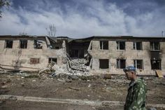 A pro-Russian rebel walks past a building at the destroyed airport in Luhansk, eastern Ukraine, September 14, 2014.  REUTERS/Marko Djurica