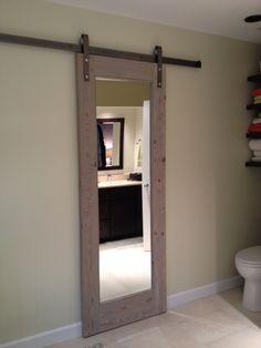 Sliding bathroom door.  Gray toned antique wood.