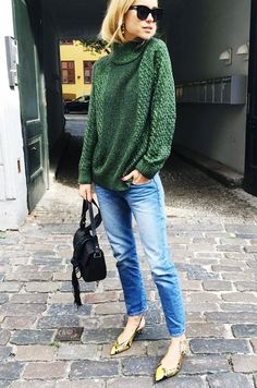 Pernille Teisbaek wears a green turtleneck sweater with blue jeans, a saddle bag, and slingback snake-print pumps
