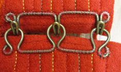 Långt häktpar på kjol från Boda, Dalarna. Tre hakar respektive hyskor har formats en längre mässingstråd.