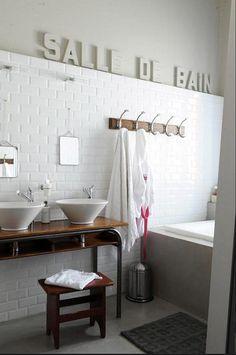 vintage school desk repurposed to a bathroom vanity. subway tile, vessel sinks