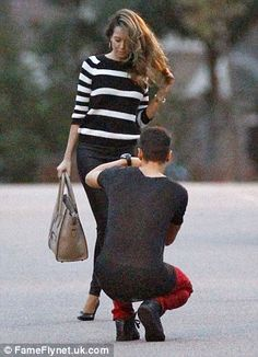 Say cheese! Mandy Capristo poses for Arsenal star Ozil who seems happy to take the snaps in the middle of a road in London