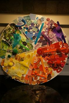 """Co-created Colour Wheel using magazine cutouts, pom-poms, beads, craft sticks, recycled bottle tops, feathers, buttons, paint charts, stickers, pipe-cleaners etc - from Playful Learning in the Early Years ("""",)"""