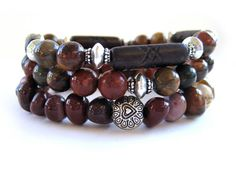 Stunning beaded stretch bracelets featuring 8mm red creek jasper beads, 22mm brown/black tube carved bone beads, moukalite chunk beads with pewter and silver plate accent beads. The gorgeous colors of the red creek jasper beads blends beautifully with the moukalite beads. These handmade bracelets can be worn stacked as shown or individually for a different look. You can even stack more bracelets with them for an entire arm party! Handmade by Rock & Hardware Jewelry