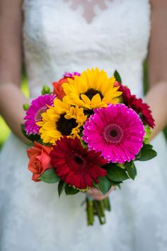 Jessica carried a vibrant bouquet with bright pink and red gerbera daisies, coral roses and sunflowers.