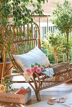 Butaca de mimbre en terraza con árbolitos