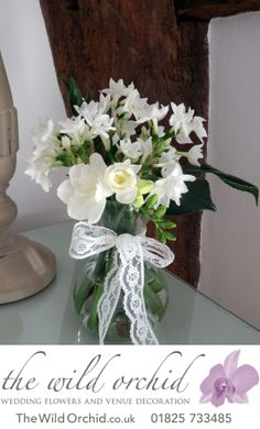A small posy of white narcissus, ivory freesia and the glossy leaves of the camellia look lovely in these small vases with lace ribbon.