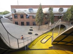 A playful network of large pipes containing walkways and bridges wraps around this children's community centre in Beijing by local practice We Architech Anonymous (WAA), housed in a series of refurbished 1970s industrial buildings.