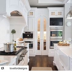 I am in love with this. Love everything about it: the cabinets, the custom cabinet hood, the arched pantry doors with the glass, the tv/double oven setup, how built-in the entire space is all the way up to the ceiling. I LOVE this.