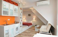 chambre salon dans une aire ouverte - lit blanc sur plate-forme, canapé blanc clic-clac et kitchenette en blanc et orange