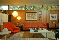 Mid-Century Modern. Knotty pine walls with warm furniture and white accents.