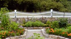 Lovely garden incorporating all my favorite elements.  Picket fence, stone walls, and gravel
