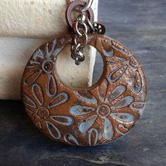 From Artgirl56 - Rustic oval stoneware pendant hand cut, carved, and impressed with groovy flowers. Glazed in a pretty Desert Sky blue matte glaze. Pretty spotting