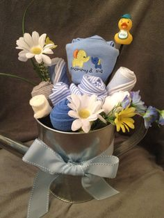 """""""Mommy and Me"""" baby boy onesie bouquet. This unique gift can be given as a baby shower gift to a welcoming family or can also be used as baby shower decor. This gift is sure to be the WOW factor at the party. It will truly be a gift you will be """"Happy to Give"""". It includes:    2 onesies  2 bibs  3 pairs of socks  2 baby wash cloths  1 duckie  accent flowers  reusable metal watering can"""