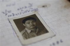 In this photo taken, July 18, 2014, an ID photo of Poch Younly is placed on his dairy displayed at the Documentation Center of Cambodia in Phnom Penh, Cambodia. (AP Photo/Heng Sinith) ▼9Aug2014AP|Khmer Rouge diary: 'Everyone works like animals' http://bigstory.ap.org/article/khmer-rouge-diary-everyone-works-animals #Documentation_Center_of_Cambodias_office #Poch_Younly