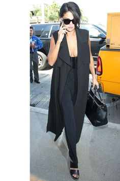 Selena Gomez's sleeveless vest is the ultimate transitional piece—she throws it over a jumpsuit on a warm day, but it can easily be worn over a knit, or belted as a dress.