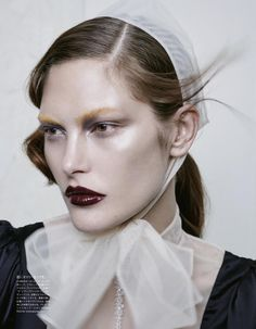 Model Catherine McNeil wears glossy dark red lip color
