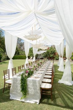 For a romantic touch - white lace parasols hang above a long reception table ~ https://www.insideweddings.com/weddings/romantic-vintage-inspired-outdoor-bridal-shower-with-pastel-decor/736/