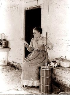 Multi-tasking, 19th century style: lady in 1897 gets some butter churning in while reading.
