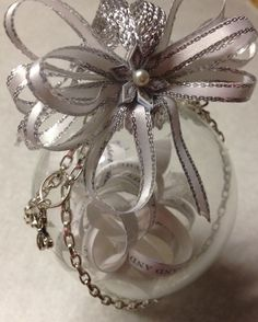 My version of a wedding keepsake ornament. The invitation was in white and silver with snowflakes, so I incorporates those colors into the ribbon and added snowflake embellishments. I also added the chain, cross, and word love to give it more depth as it is a little hard to read the lines of the announcement.