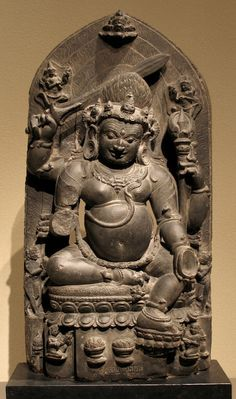 Mahakala a wrathful form of Shiva Bhairava wielding a sword and trident and displaying a skull cup (kapala); his missing fourth hand likely held the flaying knife. He wears a skull diadem with radiating flames. A skull garland around his waist, snakes form his sacred cord and armbands 11-12th C. Pala Period India 20w Mahakala - 11th-12th Century Pala Period Black Stone Sculpture