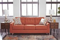 Menga Sofa - If you stand for uncompromised style, you'll love sitting on the contemporary Menga sofa. Upholstered in a fabulous rust color on feel-good fabric. Accent pillows are vivid with a snazzy geometric design in orange, blue, green, and gray. Welting on the sloping arms reflects attention to detail. Reverse and fluff up the back and seat cushions to keep them plush and supportive.