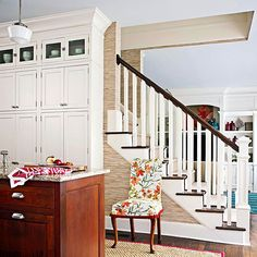 Papering a nearby staircase with grass cloth wallpaper infuses an open kitchen plan with organic texture. The neutral backdrop allows custom woodwork and little pops of color to shine.