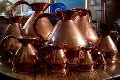 A rare collection of nine copper haystack measures, c 1830s.  These jugs were originally made to measure ale, cider and other spirits in pubs and have the size stamped to the side of each pitcher.  Made of copper with original handles, lead stamps and brass labels.  The wide rims suggest that these