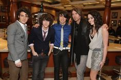 Miley with her dad and the Jonas Brothers